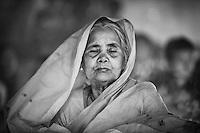 A veiled elder woman is absorbed in prayer during  the Kartik Brati or Rakher Upobash religious festival in Barodi,  Near Dhaka, Bangladesh