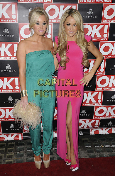 Gill O'Toole & Debbie O'Toole.The Hybrid & OK! Magazine London Fashion Week Party, Jewel Bar, Glasshouse St., London, England..February 22nd, 2012.full length pink dress strapless green hand on hip jumpsuit beige clutch bag slit split.CAP/CAN.©Can Nguyen/Capital Pictures.
