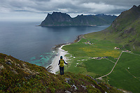 Female hiker descends Veggen mountain peak with Uttakleiv beach in backround, Vestvågøy, Lofoten Islands, Norway