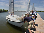 062410tvhelpinghand.Other sailors help slow the forward momentum of this sailboat as it approaches a floating dock at Carlyle Lake..BND/TIM VIZER