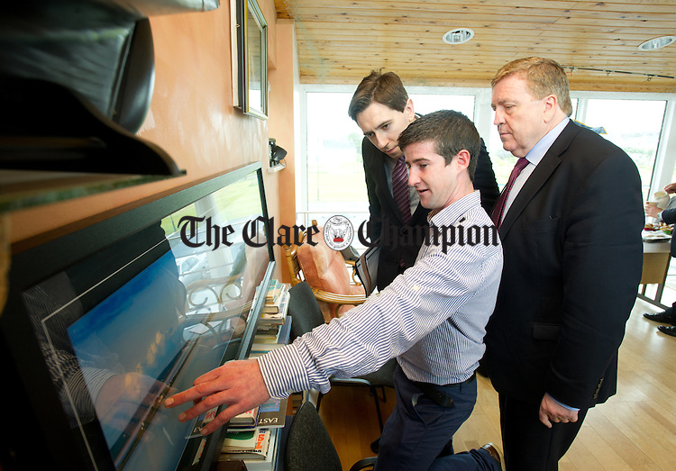 Simon Harris TD, Minister of State at the Departments of Finance, Public Expenditure and Reform and Pat Breen TD Chairman Oireachtas Committee on Foreign Affairs and Trade are shown a photo of Scattery Island by Diarmuid Whelan, Chairperson Scattery Island Tourism and Heritage Group during their visit to Kilrush Marina. Photograph by John Kelly.