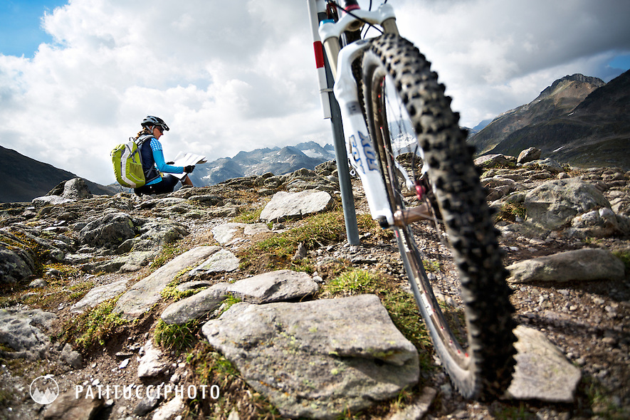 Female mountain biker stopped in the Swiss Alps looking at a trail map for directions on the Sertig Pass