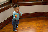 MR / Schenectady, NY. Toddler (1 year and 2 months old, African-American and Caucasian) in early walking stage stands while eating a cracker. MR: Dal4. ID: AM-HD. © Ellen B. Senisi