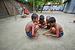 Children play with stones in Kunderpara, a village on an island in the Brahmaputra River in northern Bangladesh. Their mother, Rogina, who uses only one name, cooks over a fire in the background. Severe flooding in August 2017 destroyed the island's crops but ICCO Cooperation, a member of the ACT Alliance, provided emergency food and seeds so that Rogina and other islanders could replant their food crops and restart their lives.
