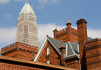 The Bank of America corporate headquarters building towers over a church in uptown Charlotte, NC.