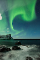 Northern lights fill sky over sea, Flakstadøy, Lofoten Islands, Norway