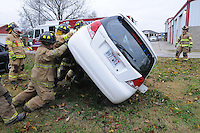 NWA Democrat-Gazette/FLIP PUTTHOFF <br /> CUTTING EDGE<br /> Centerton firefighters team up Saturday Nov. 21, 2015 to turn a car over on its side to practice with hydraulic cutting and prying tools during auto extrication training at the fire station. Firefighters practiced with a tools designed to rescue drivers and passengers from vehicles. The equipment is on board a truck the department received in August, said Matt Thompson, assistant chief.