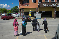 "January 15, 2015 - Rawang (Malaysia). Global Ikhwan's CEO Lokman Hakim, walks to his car together with 3 of his 4 wives and 2 of his 27 children. Although polygamy is legal in Malaysia, it is rarely practiced in the open or with the knowledge and approval of all the wives involved in such a relationship. However, Global Ikhwan - only employs women, who view polygamy as the integral element of ""the Islamic way of life."" © Thomas Cristofoletti / Ruom"
