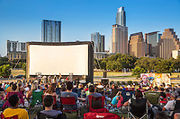 Austinites sit on blankets as they enjoy the outdoor movies and live music on a hot summer's night in downtown Austin, Texas. View from behind.
