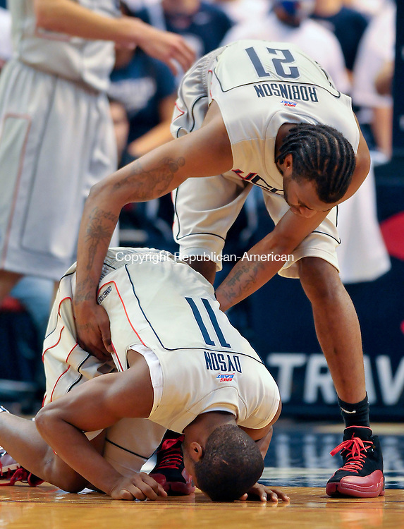 HARTFORD, CT- 30 JANUARY 2010-013010JS07--UConn's Stanley Robinson (21) tries to help up his teammate Jerome Dyson (11) after Dyson was injured during their 70-68 loss to Marquette Saturday at the XL Center in Hartford. <br /> Jim Shannon Republican-American