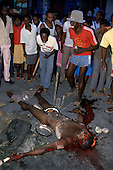 Port-au-Prince, Haiti<br /> November 1987<br /> <br /> Haitians celebrate the public dismembering of a suspected ton-ton-macoute prior to the elections to be held on November 29th, the first attempt at a democratic election in Haiti. It was unsuccessful as 34 people were killed at a polling station and elections were moved up to February 1988.<br /> <br /> Leslie Fran&ccedil;ois Manigat won the election with many political parties boycotting. He had military backing but once in office he sought greater control over the military in an effort, to fight corruption. Manigat's government was overthrown by General Henri Namphy within months.