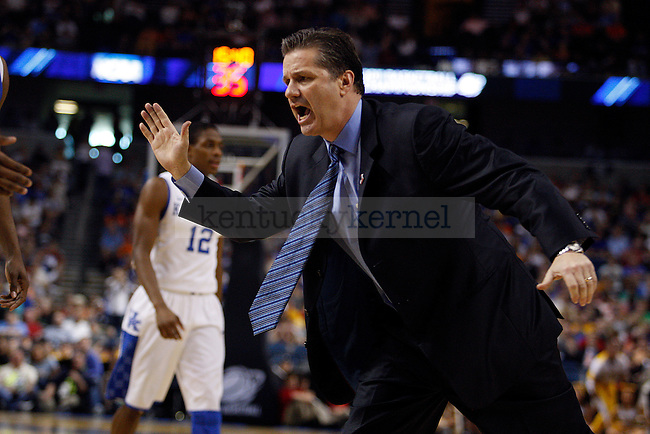 Uk head coach John Calipari high fives DeAndre Liggins as he comes off the court in the second half of UK's second round NCAA tournament win, 71-63, against West Virginia at the St. Pete Times Forum in Tampa, Florida on Saturday, March 19, 2011.  Photo by Britney McIntosh | Staff