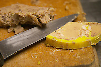 A slice of duck liver foie gras and a cutting knife on a wooden cutting board Ferme de Biorne duck and fowl farm Dordogne France Workshop on how to make foie gras duck liver pate and other conserves