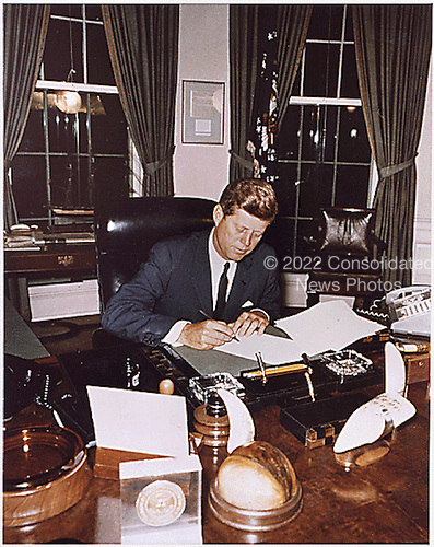 United States President John F. Kennedy signs Cuba Quarantine Proclamation at his desk in the Oval Office of the White House in Washington, DC on October 23, 1962. <br /> Mandatory Credit: Robert Knudsen/White House via CNP
