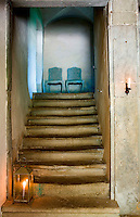 A pair of reproduction 18th century blue painted chairs on the landing of the stone staircase