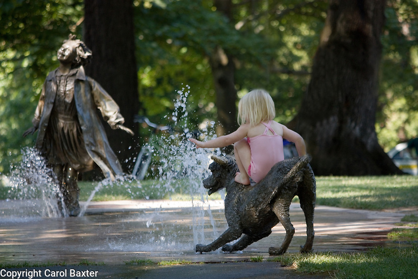 A small statue of a dog provides a perfect seat for a young girl to enjoy the bubbling fountain.