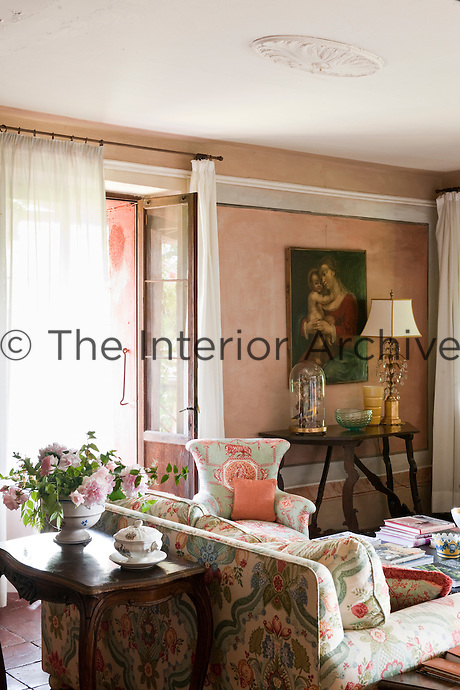 Floral patterned furniture is complimented by a rose-coloured wall finish in this Italian country house