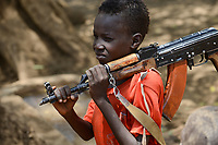 ETHIOPIA, Southern Nations, Lower Omo valley, Kangaten, village Kakuta, Nyangatom tribe, boy with machine gun Kalashnikov AK-47 for protection from cattle raids by neighbor Turkana warriors, the gun is marked with SSPSHQ / AETHIOPIEN, Omo Tal, Kangaten, Dorf Kakuta, Nyangatom Hirtenvolk, Junge Losikiria traegt Maschinengewehr Kalaschnikow AK-47 zum Schutz vor Ueberfaellen durch Turkana Krieger