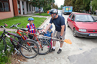 Polish dad loading newly purchased broom on his bike for a ride home with his children. Rzeczyca Central Poland