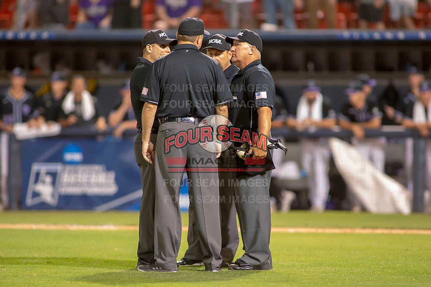 The umpires confer over an interference call during the game between the University of Washington Huskies and the Cal State Fullerton Titans at Goodwin Field on June 10, 2018 in Fullerton, California. The Huskies defeated the Titans 6-5. (Donn Parris/Four Seam Images)
