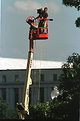 Washington, DC - August 6, 1998 -- Unidentified network pool cameraman, stationed on a cherry-picker, awaits the departure of Monica Lewinsky from U.S. District Court this afternoon..Credit: Ron Sachs / CNP