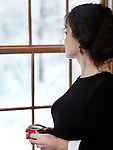 Woman with a cup of coffee looking out of the window with a snowy winter scenery behind it