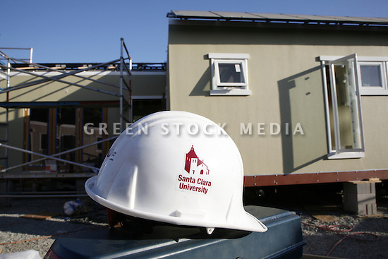 A hard hat with the Santa Clara University logo sits in front of the SCU 2007 Solar Decathlon team's solar home under final stages of pre-competition construction.