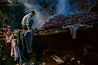 Giang A Cho, a black cardamom (Thao Qua) farmer, checks the seed pods as they dry above a fire on a shelf made of freshly cut bamboo poles. The dried pods are about one third of their original weight, making them easier to transport out of the jungle.