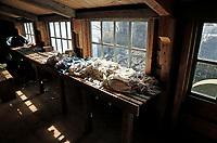 Nederland Westzaan 2017 . De Schoolmeester te Westzaan is de laatste papiermolen ter wereld die op windkracht functioneert. De molen werd oorspronkelijk in 1692 gebouwd en is tegenwoordig nog dagelijks in gebruik. Er wordt op ambachtelijke wijze Zaansch Bord, een papiersoort, vervaardigd. De eigenaar is sinds 1976 de Vereniging De Zaansche Molen. De molen is als zeskant opgetrokken. Vodden liggen op een tafel. Het scheurhok. De vodden worden als grondstof gebruikt voor de papierfabricage.   Foto Berlinda van Dam / Hollandse Hoogte