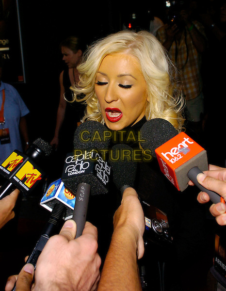 CHRISTINA AGUILERA.Arrivals at Koko in Camden Town for Christina Aguilera's London gig, London, UK..July 20th, 2006.Ref: CAN.headshot portrait microphones red lipstick funny face.www.capitalpictures.com.sales@capitalpictures.com.©Can Nguyen/Capital Pictures
