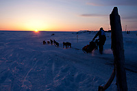 Ken Anderson runs on the trail just outside Nome as the sun sets over the Bering Sea during the 2010 Iditarod