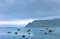 Moored fishing boats and yachts in tranquil sea scene on the Isle of Skye, Western Isles of Scotland, UK