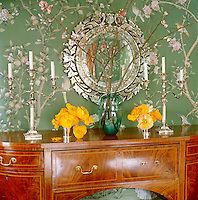The green floral wallpaper in the dining room is hand-painted and based on a traditional Chinoiserie pattern and the antique Venetian mirror hanging above the sideboard was a Paris flea-market find