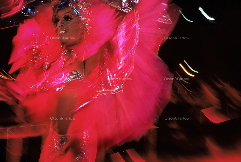 Scantily clad women in feathers and heavy makeup parade down the aisles through the audience at the Tropicana nightclub. The dancers entertain at the infamous pre-Revolutionary cabaret wearing flamboyant headdresses with glowing chandeliers and ostentatious sequined outfits embellished with feathers. Since New Years 1939, the show has featured more than 200 performers in dance and song numbers on stages at various outdoor stages