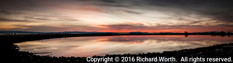 Early in the sunset process, soft pastel colors fill the sky and are reflected in the waters of the lagoon adjacent to the San Leandro Marina Park.