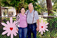 RACHEL DICKERSON/MCDONALD COUNTY PRESS Patsy Ward, left, and Ed Malcolm of Pineville have found romance together after both lost their spouses and after knowing each other for a lifetime. They are pictured next to some of the larger examples of wooden flowers that Malcolm makes.