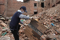 A man collects items from his destroyed house in Shanku, near Kathmandu, Nepal. May 9, 2015