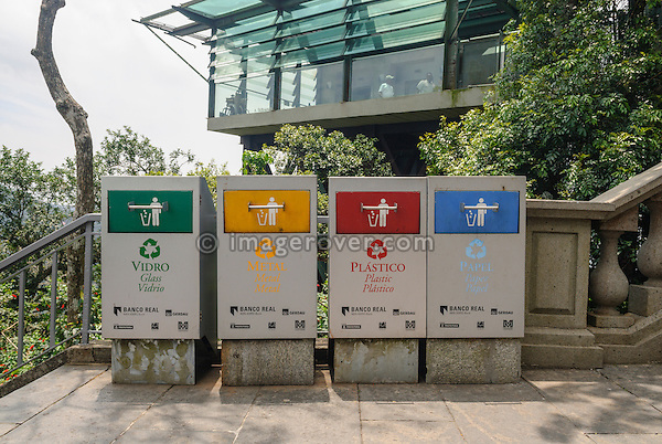 Rio de Janeiro, Brazil. Four coloured waste bins lined up: green for glass (vidro), yellow for metal, red for plastics (plastico), blue for paper (papel).