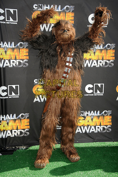 CHEWBACCA.1st Annual Cartoon Network Hall of Game Awards held at Barker Hangar, Santa Monica, California, USA..February 21st, 2011.full length costume fur brown star wars arms in air.CAP/ADM/BP.©Byron Purvis/AdMedia/Capital Pictures.