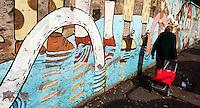 an elderly woman with shopping cart walking in front of a mural - Una donna anziana passa davanti il murale con il carrello della spesa <br /> Artist Agostino Iacurci <br /> Title La Conquista dello Spazio . The conquest of space<br /> Quartiere / District  Ostiense <br /> <br /> Roma 10-11-2015 Street Art a Roma. <br /> Street Art in Rome. <br /> Foto Andrea Staccioli / Insidefoto