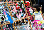 A young girl looks at Edo furin, or glass wind chimes, displayed on a wooden frame by seller Yoshitomo Sasaki in the chic Ginza district in Tokyo, Japan. The chimes, which date back more than 200 years in Japan, were traditionally carried around town dangling from  bamboo poles by sellers. Sasaki is one of a few people who continue this trend.