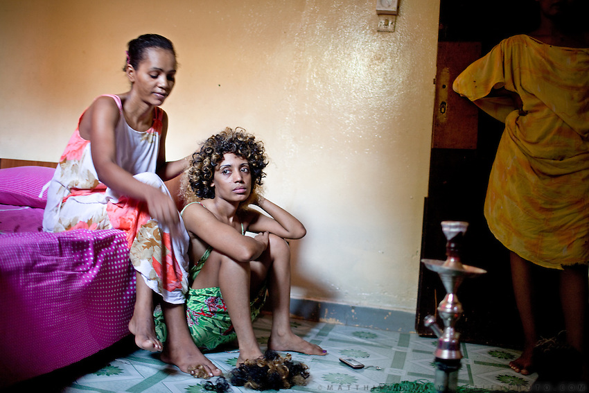 Muna is combing Tina's hair; the two Ethiopians prostitutes will soon be  heading to a