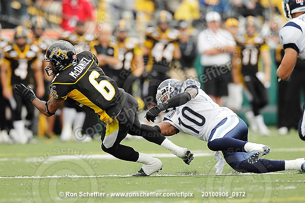 September 6, 2010; Hamilton, ON, CAN; Hamilton Tiger-Cats wide receiver Marquay McDaniel (6) stretches for extra yards ahead of Toronto Argonauts safety Willie Pile (10). CFL football: Labour Day Classic - Toronto Argonauts vs. Hamilton Tiger-Cats at Ivor Wynne Stadium. The Tiger-Cats defeated the Argonauts 28-13. Mandatory Credit: Ron Scheffler.