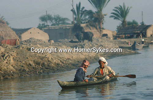 Marsh Arabs. Southern Iraq. Circa 1985. Marsh Arab men in boat banks of river Tigris. Haur al Mamar or Haur al-Hamar marsh collectively known now as Hammar marshes Irag 1984
