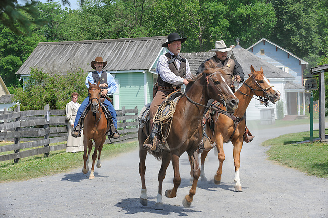 Marshall and two deputies riding into town on horses down a dirt Main street in the American Wild West, modern day reenactment.