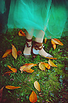 Young woman wearing dancing shoes<br /> Cropped photo of a dancer wearing a green tulle skirt with her slippers in some pretty autumn leaves