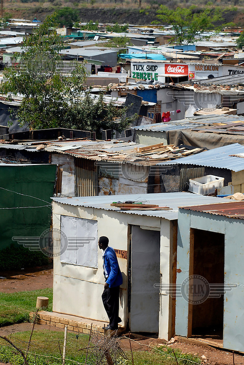 A man stands at the doorway of a shack, one of many rough, self-built dwellings, in Nellmaius, Mamelodi township.