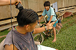 A man looks at his reflection in a broken mirror while receiving a  hair cut in the yard outside his thatched hut in the Mayan village of Midway, Belize.  A boy on a bike looks on. The razor is electric, a new feature with the introduction of electricity a few years ago.