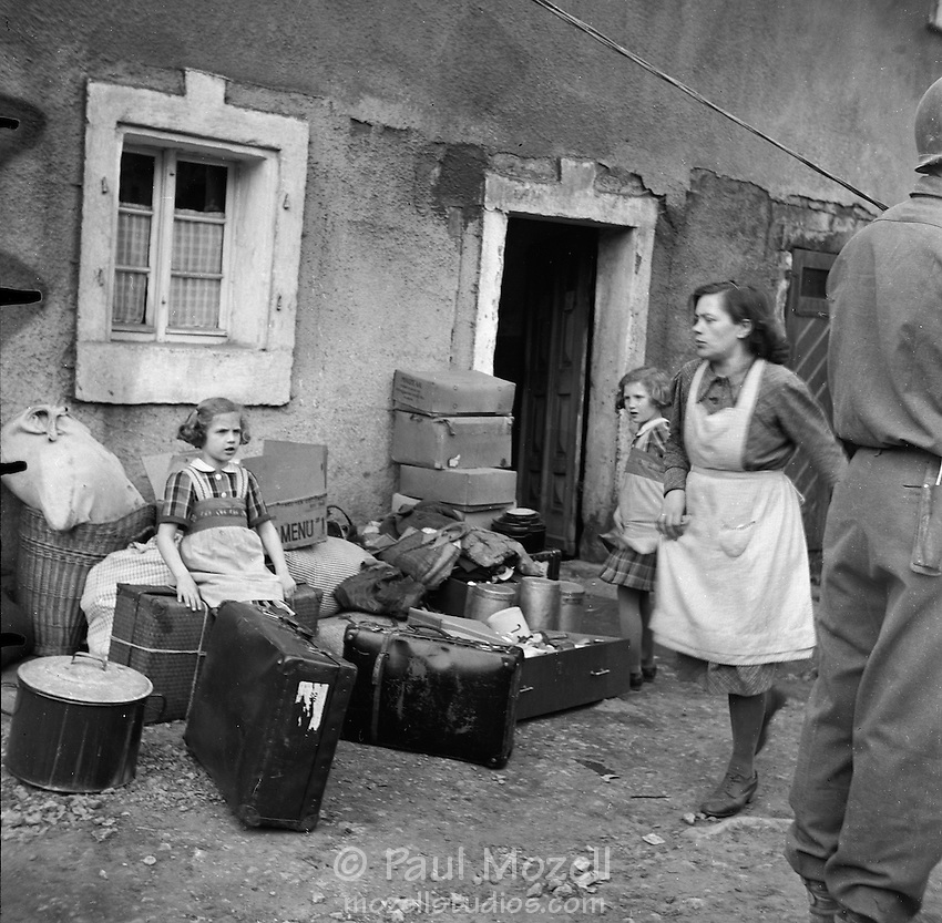 German family packs their belongings to be temporarily relocated while American troops use their housing.
