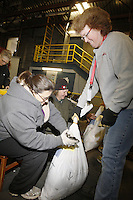 Wednesday, February 13, 2013.  Volunteers Maureen Pedigo, Debbie Doherty and Jennifer Ambrose tag musher's food drop bags at Airland Transport in Anchorage to be sent out to the 22 checkpoints along the trail.  .Iditarod 2013
